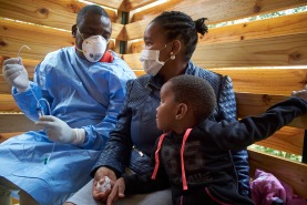 Sitting with her mother Fisislwe Motsa, Siphniwayinkosi Blamini receives sputum induction and Nasal Pharyngeal Aspirate in a well-ventilated Cough Box at the TB Clinic at Baylor Tuberculosis Centre of Excellence, Mbabane, Swaziland.