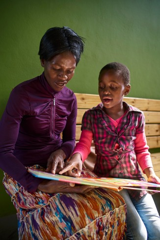 While waiting for consultation, Asianah Dlanini, 45 years old, reads from a book to Silindzile Mamba, her 8 years old daughter, in a brightly lit and well-ventilated child friendly space at the TB Clinic in Baylor Tuberculosis Centre of Excellence, Mbabane, Swaziland.
