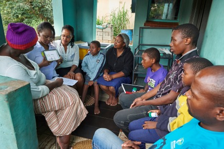 During a home visit, Bulisile B. Mzileni, Research Assistant from the TB Clinic in Baylor Tuberculosis Centre of Excellence, shows a video on TB and HIV to a family in Mangwaneni in Mbabane, the capital of Swaziland.