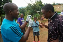 During a home visit, Mbatha, driver as well as a volunteer worker from the TB Clinic in Baylor Tuberculosis Centre of Excellence, explains children how to give sputum for TB test in Mangwaneni in Mbabane, the capital of Swaziland.