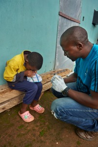 During a home visit, Mbatha, driver as well as a volunteer worker from the TB Clinic in Baylor Tuberculosis Centre of Excellence, assists a child give sputum sample for TB test using steam technique in Mangwaneni in Mbabane, the capital of Swaziland.